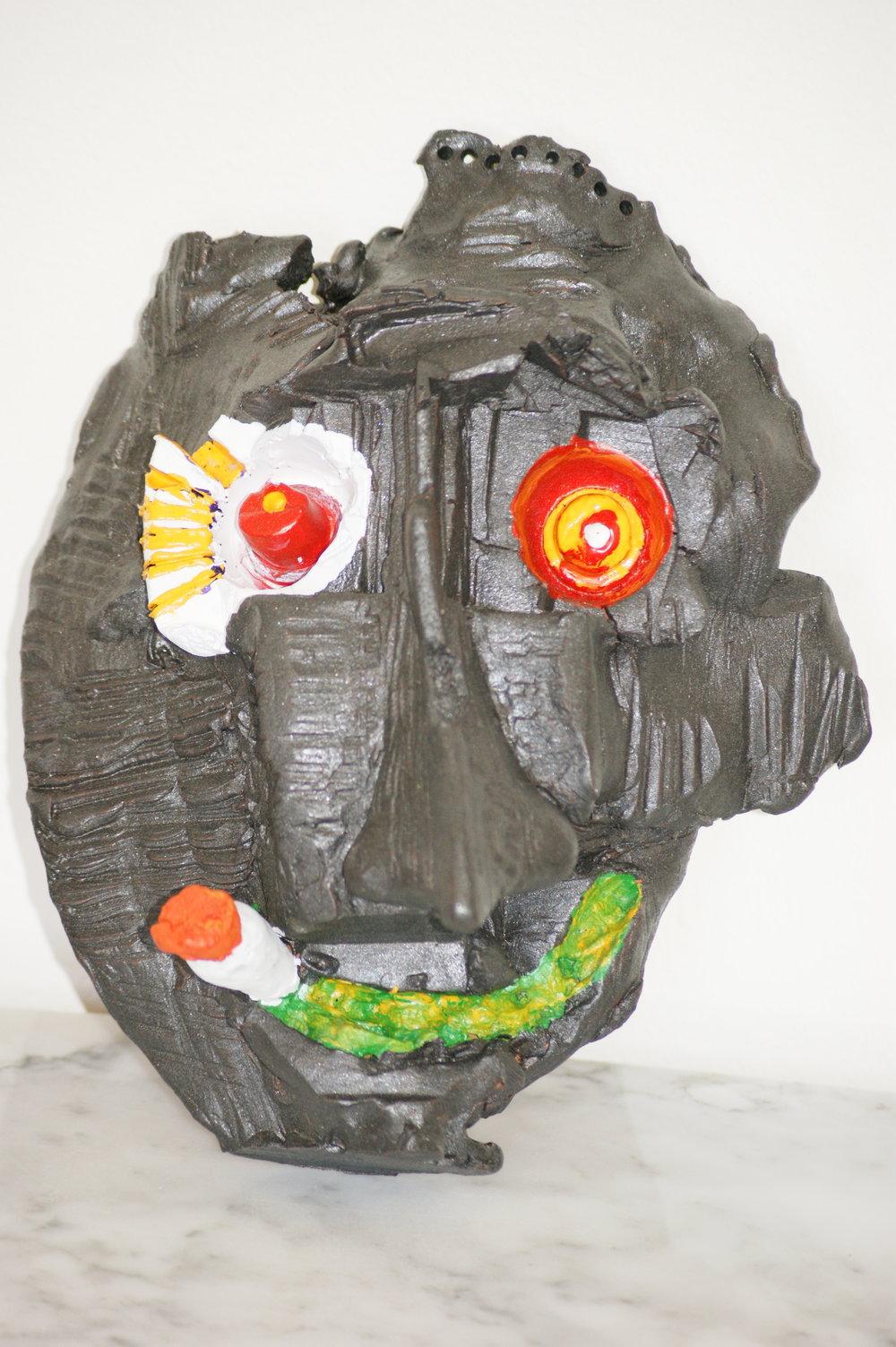 Máscara en arcilla roja cocida, 2018. Representa un marcianillo alucinado fumando un porro. Yo no fumo ni soy adepto de la marihuana, pero me he permitido hacer un guiño a mi parte más loca, gamberra e iconoclasta. Es también un homenaje al Makoki de comienzos de los ochenta que buscaba con fruición en la cuesta de Moyano y en las Ramblas, en las correrías artísticas y sentimentales de aquellos tiempos.