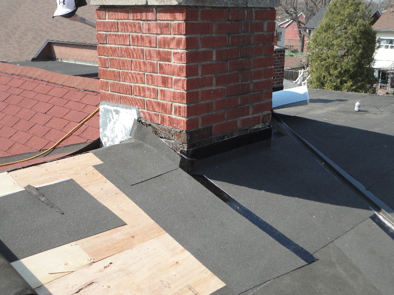 Chimney wrapped in a rubber membrane before is has metal (flashing) installed around it.