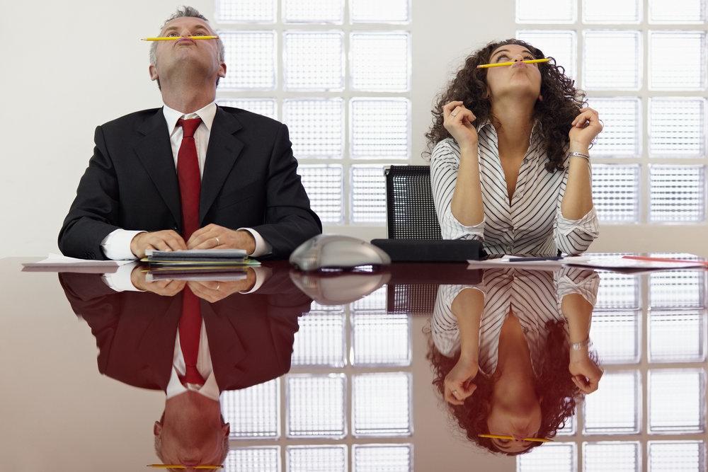 Två uttråkade personer sitter vid ett mötesbord och balanserar pennor på näsan.