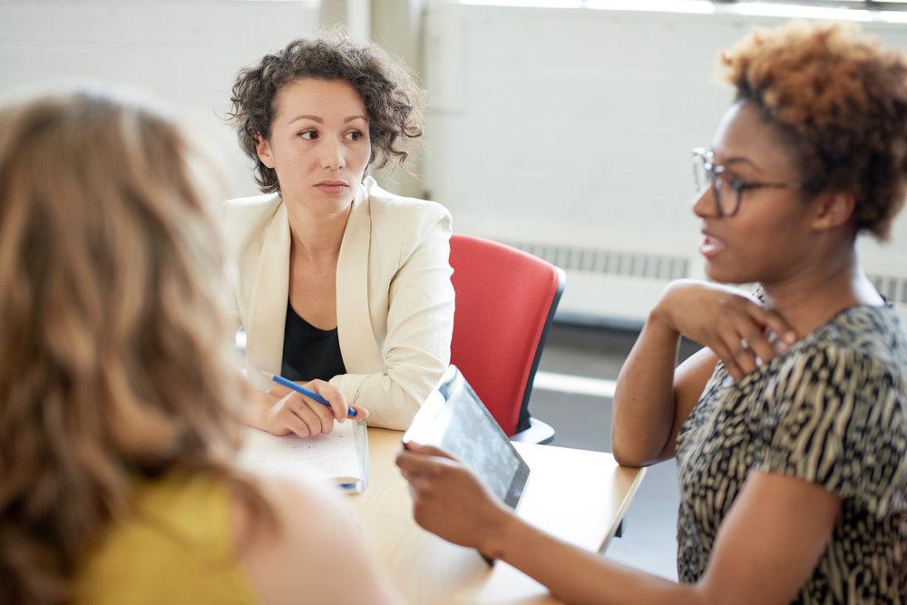 två kvinnor vid ett mötesbord. Den ena personen pratar och den andra ser skeptiskt på den som pratar.
