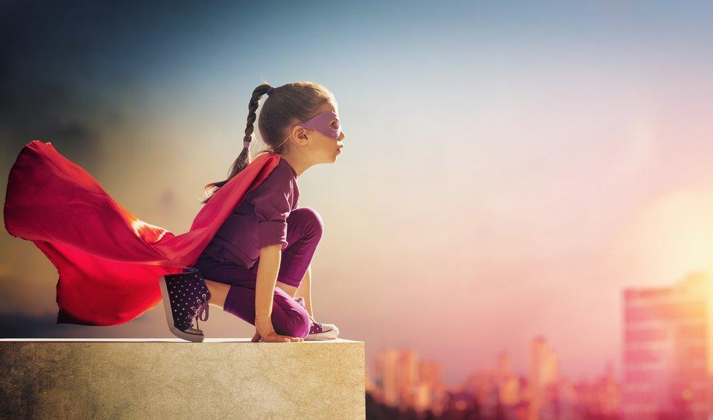 Flicka som är klädd till superhjälpte i position för att flyga