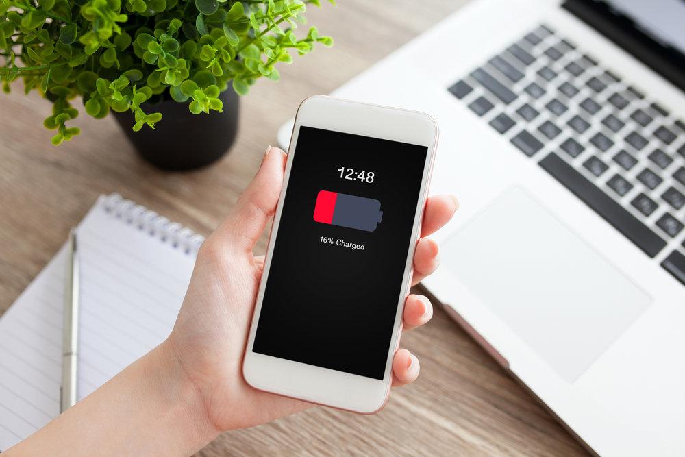 Hand som håller i en mobil som visar rött batteri. I bakgrunden syns en laptop och ett anteckningsblock