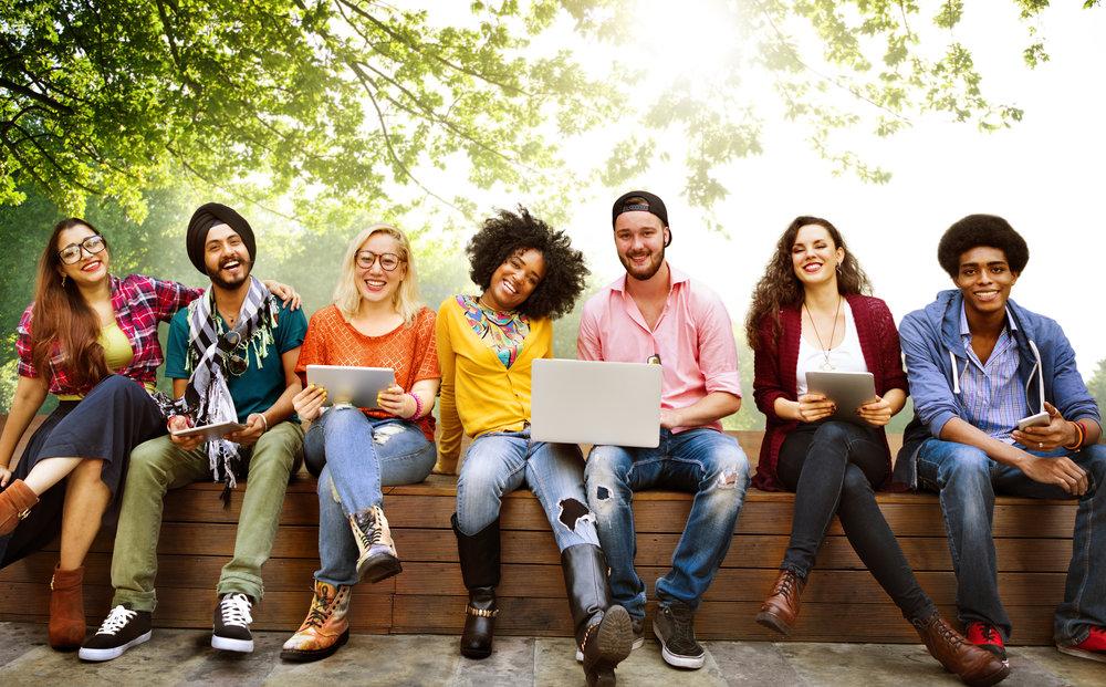 Människor med olika hudfärg och utseende sitter på en bänk. Några har laptops i knäna. Alla ler in i kameran.