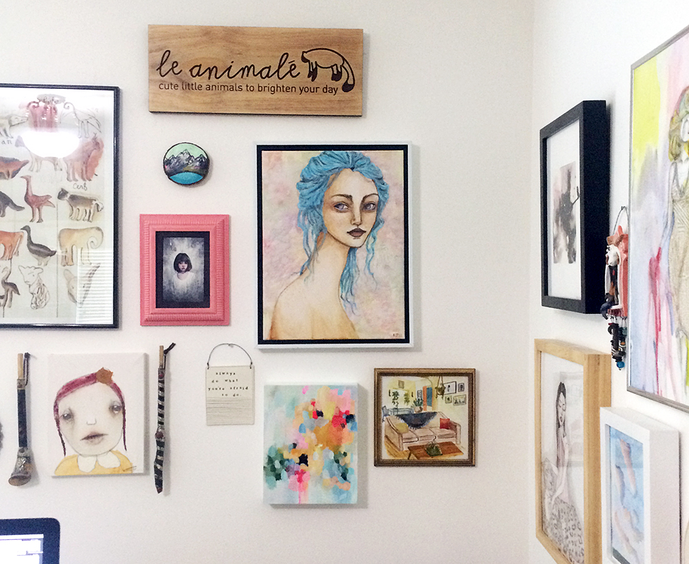 """Current arrangement in my studio. A poster from my trip to Palais Ideal in France, a portrait entitled """"Laura"""" from Christina Romeo surrounded by two Berber instruments, a watercolor painting by Ellen Wilberg, a small mountain on cedar by Cathy McMurray, my le animalé sign, a blue-haired portrait by my sister Kayla, a ceramic plaque from mbartstudios that reads, """"always do what you're afraid to do"""", newest painting from my friend Devon, and an interior painting from my friend Frances' 100-day project."""