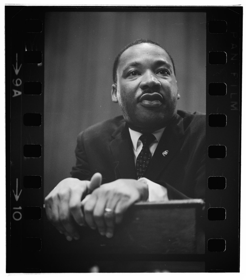 Martin Luther King, Jr. leaning on the lectern at a press conference, March 6, 1964. Photograph by Marion S. Trikosko, Library of Congress Prints and Photographs Division, LC-DIG-ppmsc-01269.