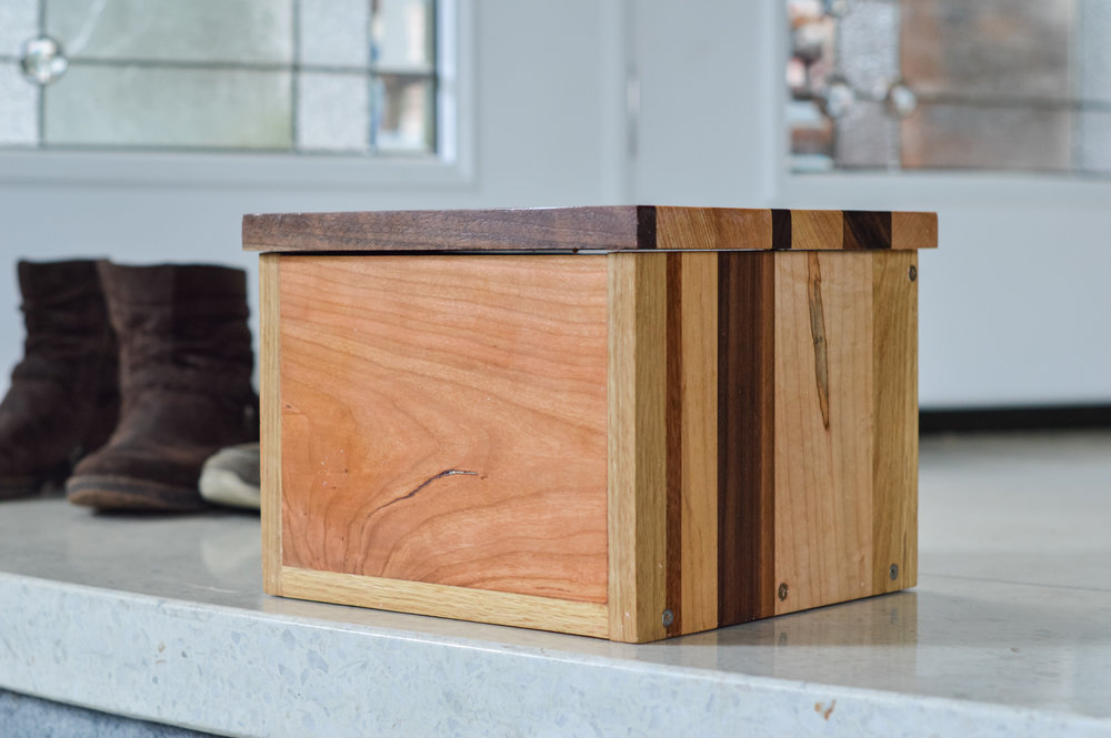 My husband gathered various woods from our workshop to make this box for the ashes.