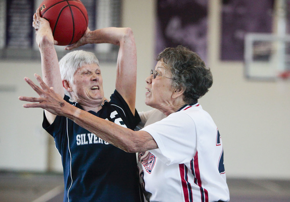Kay Poole (left) of the Silver Spirits attempts to pass the ball as Jacqueline Stephens (right) of NOVA United Classics blocks her during the National Senior Games basketball competition. This competition took place at the St. Thomas University Basketball Court in St. Paul, MN. on Jul. 9, 2015.