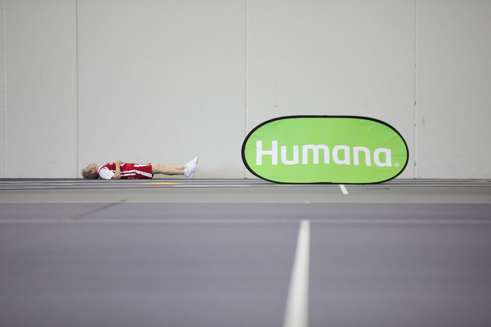 An athlete stretches next to a Humana sign during the 2015 National Senior Games basketball competition that took place on Jul. 14, 2015 at the University of St. Thomas Basketball Court in St. Paul, MN.