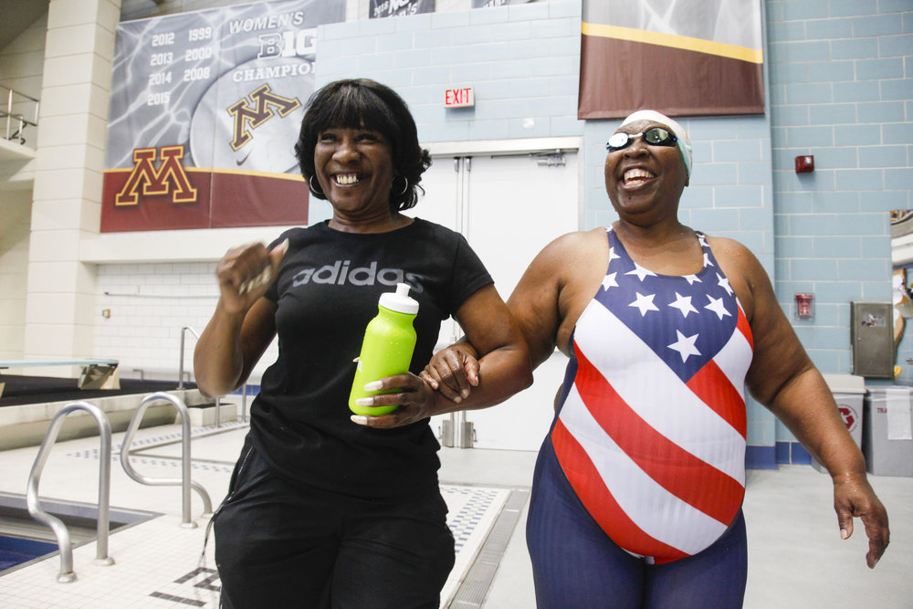 Patricia Henderson (left) dances as she guides her sister,  Vivian Stancil (right) to the bleachers during the National Senior Games swim meet that took place at the University of Minneapolis Aquatic Center in Minneapolis, MN. on Jul. 8, 2015. Stancil is legally blind and has won 188 medals in swimming. She also runs a non-profit organization and has a position on the commision board of Riverside, Calif.