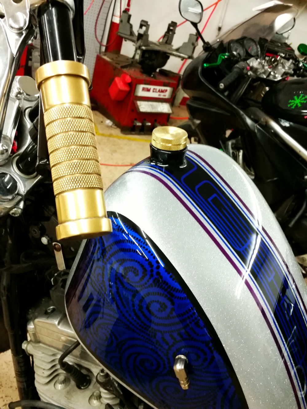 This gas tank has had quite a lot of work put in by us. Including our signature flush mount sight glass, a brass gas cap that matches our brass stepped points cover and knurled brass grips. The petcock has been relocated and all the ports on the bottom of the tank have been deleted.