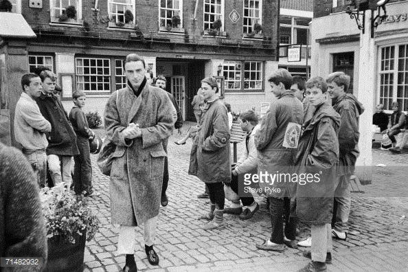 Paul Weller is watched by a group of mods in the courtyard of a pub in Oxford, 6th October 1984. Photo: Steve Pyke