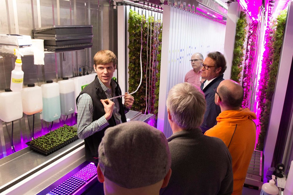 Andrew shows guests the flexible LED strips that provide the plants with all of the light energy they need to grow strong.