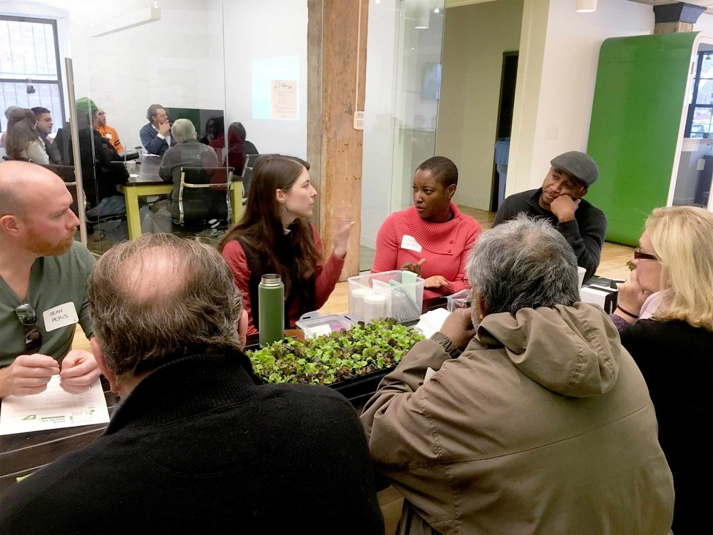 Jaime answers a question from an open house participant. She has some live seedlings on the table that were used during the session to demonstrate how to successfully transplant seedlings into the crop columns.