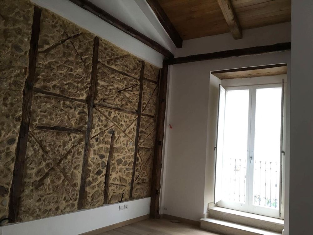 Dependance: master bedroom with original stone wall and small balcony