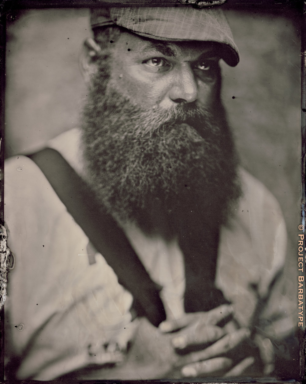 Quinton Crocker sporting a mighty fine beard, along with a newsboy cap and some spiffy suspenders.