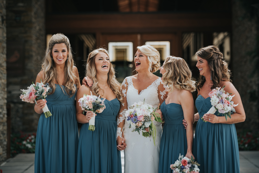 Spend about 5 minutes around me on a wedding day and you'll hear me say how much I hate the fake laugh. On a day so packed with emotional highs and lows, photographers who ask their clients to laugh aren't plugged in enough. These moments when our bridesmaids laugh are real, the reactions are real, the emotions are real. Group dynamics can be tricky because every group is pretty unique. The key is the same, find the alpha, connect with them, and then poke fun just a little. The group will relax when they realize you're willing to get involved on their level. Group shots can have a variety of looks so I carry a lot of lens options with me when shooting them. 35mm, 50mm, 85mm, 70-200mm.
