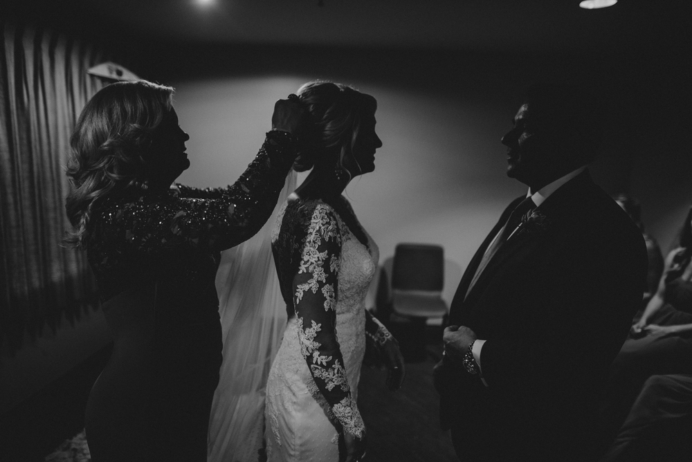 I'm a huge fan of shooting in the light I have. Our minds have a way of associating light with memory and the minute you start manipulating candid moments you've lost some of the authenticity. This shot was just seconds before the ceremony started and is actually Shelby (the bride) giving her dad a pep talk (instead of the other way around). This family is incredibly tight nit and images like this of mom and dad together in the frame can carry a lot of emotional power. I'm almost always carrying a 50mm or 85mm for this kind of work because I want the speed of a prime and just a little bit of distance so that I don't interrupt.