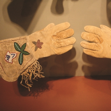 This particular pair of gauntlet gloves is Native American-made and was crafted from naturally tanned deer or elk leather, making them soft yet durable.