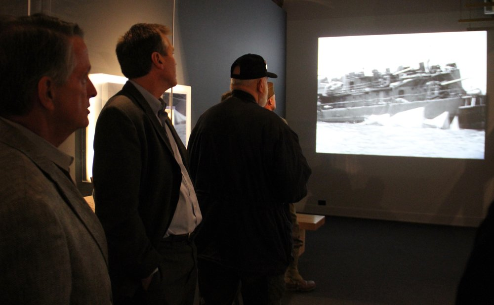 Visitors watch film reels in the Personal Stories of Pearl Harbor exhibit