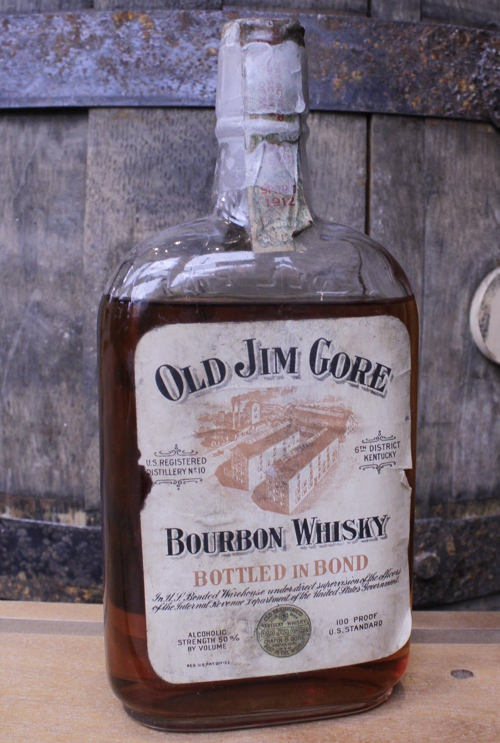"""OLD JIM GORE BOURBON WHISKY    About the Product   One pint of Kentucky bourbon (100 proof), aged 13 years, bottled in bond. Distilled in spring 1912* by Wiglesworth Bros. Co. Bottled in fall 1925* by James E. Pepper & Co.  Named after one of its Chicago-based proprietors [Chapin & Gore] and advertised as the """"Best in the World,"""" this old-fashioned sour mash bourbon has a rare mellow flavor.   About the Distillery   6th Dist., RD #10, Wiglesworth Bros. Co. (1869 – 1919). Harrison County, Kentucky, USA.  Located on the South Fork of the Licking River four miles northwest of Cynthiana, this distillery was built in 1856 by John Poindexter. In 1869 the Wiglesworth family acquired it, tore it down and rebuilt it. By 1910 the mashing capacity had been increased to 300 bushels per day, and there were three bonded warehouses with a storage capacity for 20,000 barrels. In the late 1910s the officers were J. M. Wiglesworth, president and W. T. Wiglesworth, secretary-treasurer. Products included Old G. W. Taylor, Poindexter Bourbon, and Wiglesworth Bros. Sweet Mash. The distillery closed at Prohibition.  In 1924 all the whiskey in storage was transferred to the concentration warehouses of James E. Pepper & Co., a facility in Lexington that had been leased in 1907 for 20 years by Joseph Wolf of Chicago, where it was bottled for medicinal spirits."""