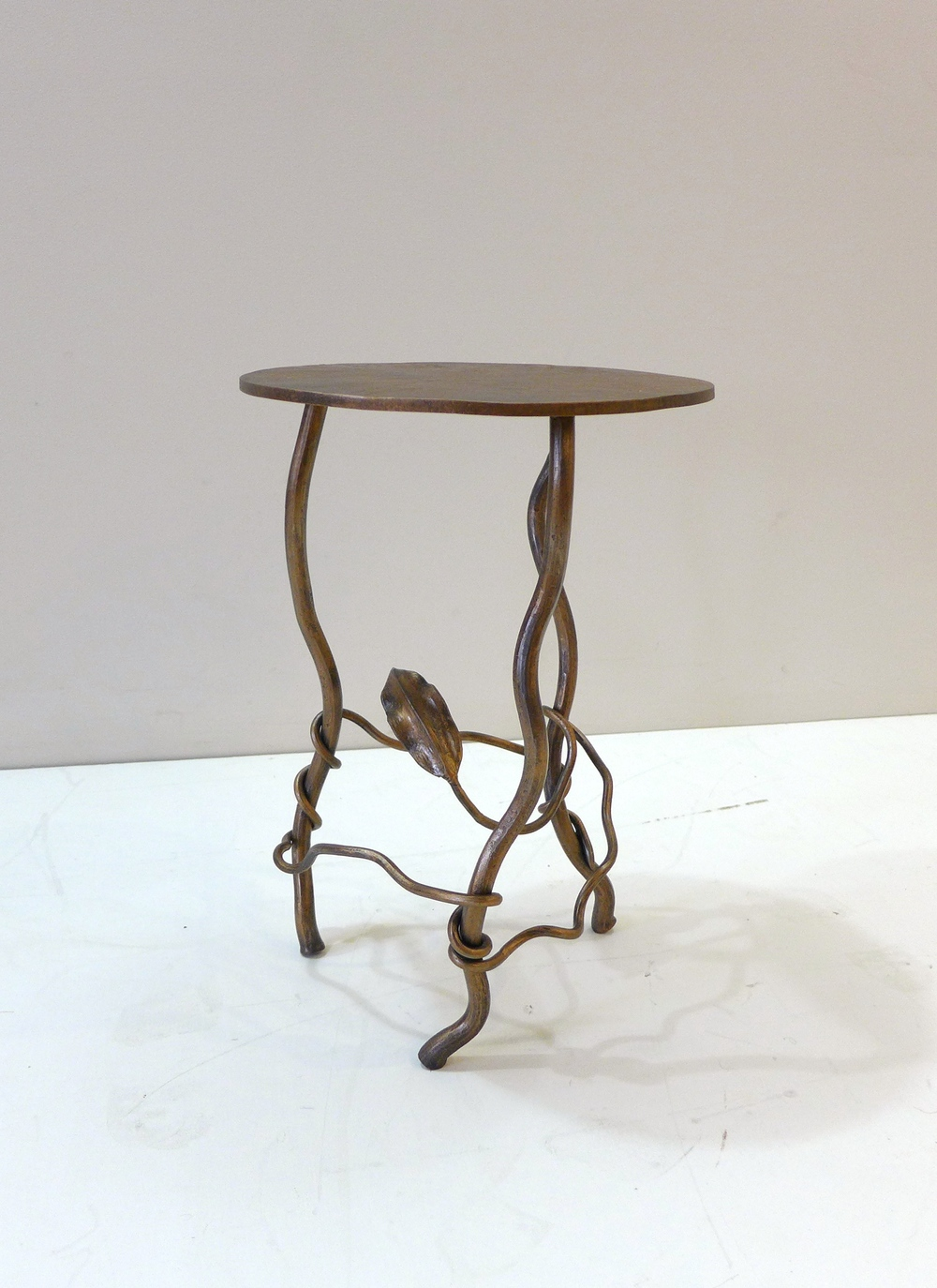 Painted steel single disc side table with leaf and vine