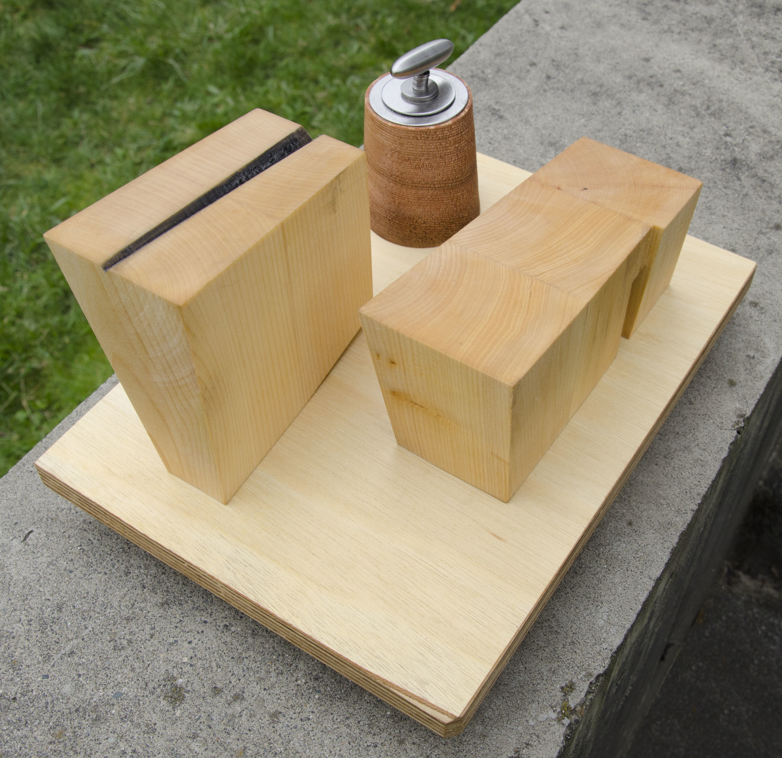Multi lam plywood base with scrap wood runners below.  Cedar machine base, stainless steel washers and lozenge with hidden brazed rod epoxied into cedar, basswood buildings, carbon applied to notch cut into one building for beam rail path into space. Maybe for measuring the space/time continuum?  7 x 12 x 6.25h inches.