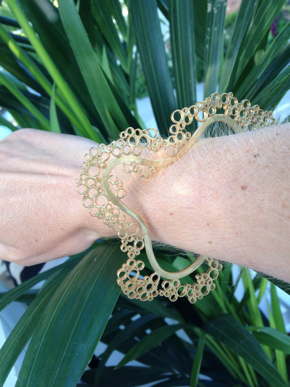 My Fizz bracelet in gold, handmade in Sterling silver with 18K gold plating, against the Chelsea Flower Show greenery