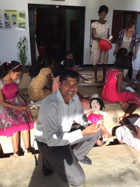 Mr. Eshantha Arlyadasa holding a doll made by Betty