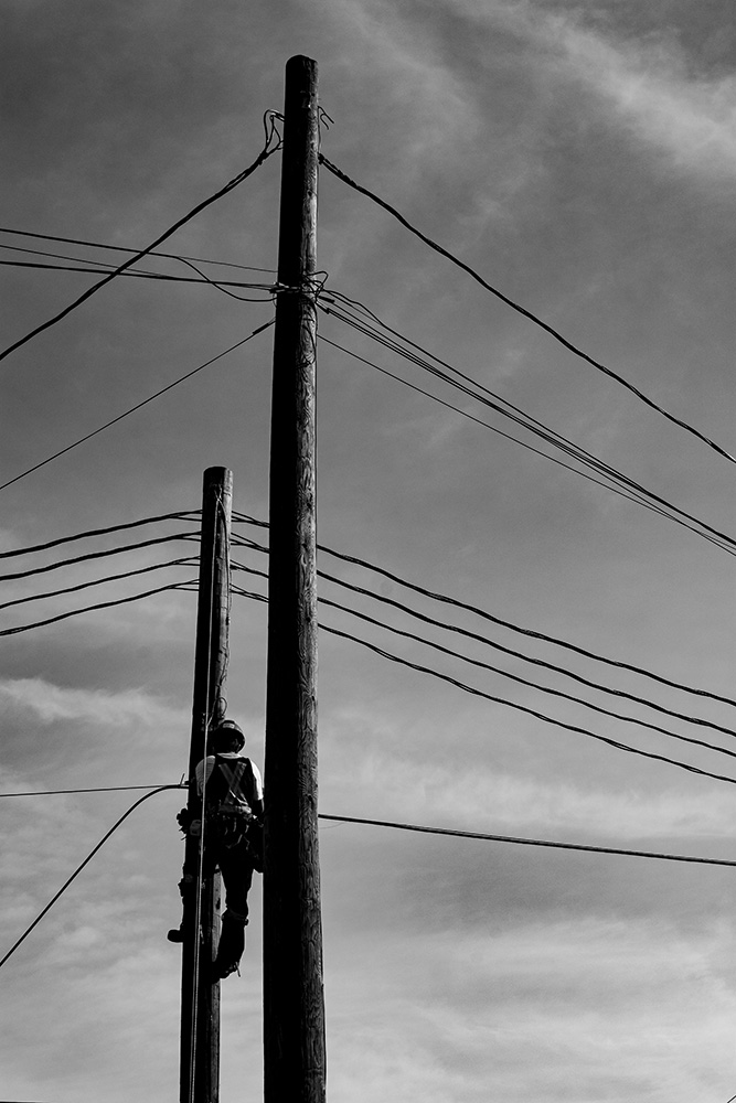 August 2016: A lineman is framed by poles and wires