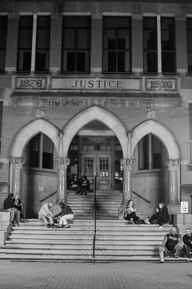 September 2016: People lounge on the steps of the Fredericton courthouse during Harvest Jazz and Blues Festival