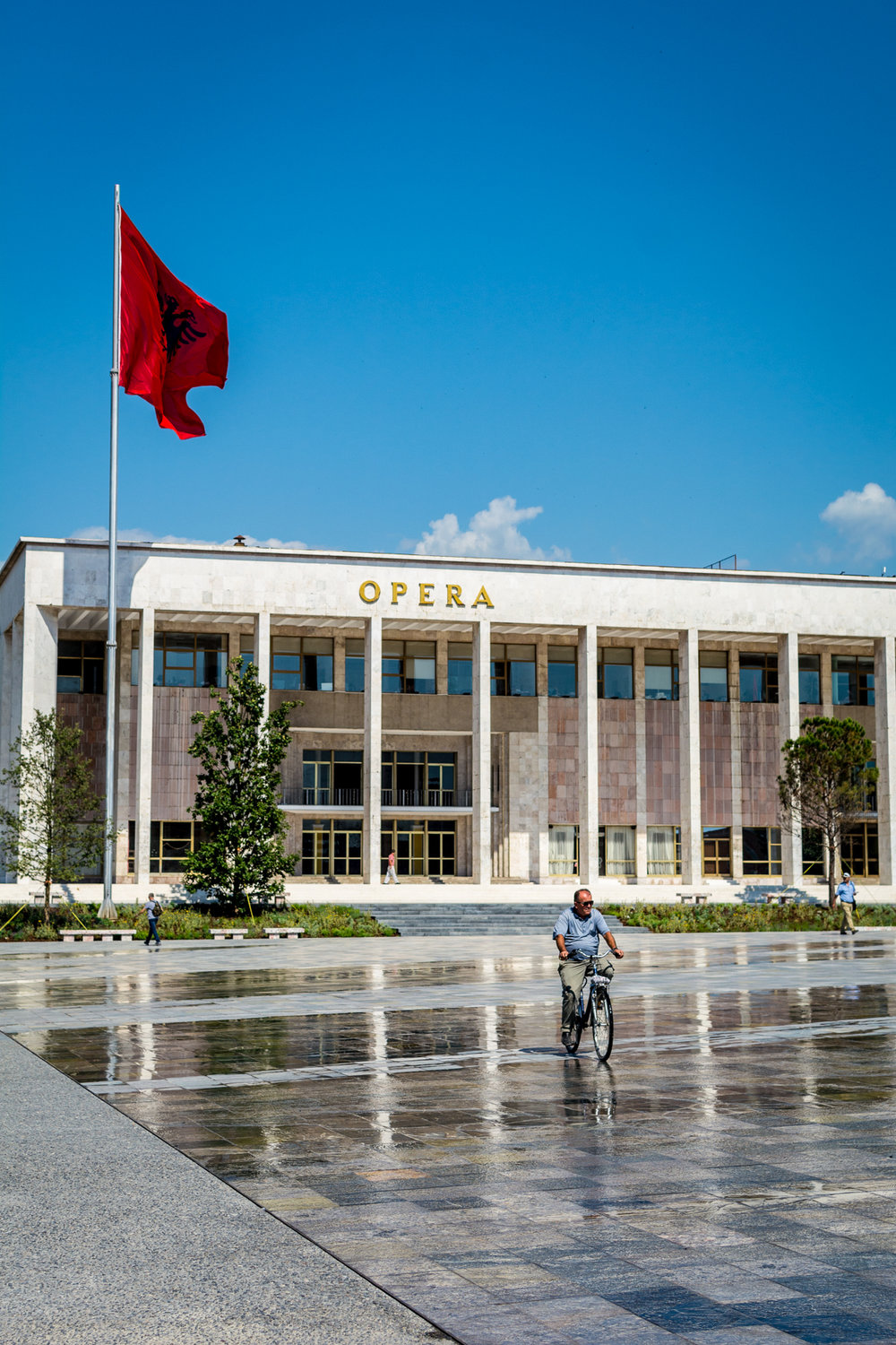 A man cycles through Tirana's main square. The stone tiles are meant to represent the different areas of Albania and are kept wet to show their full colour.