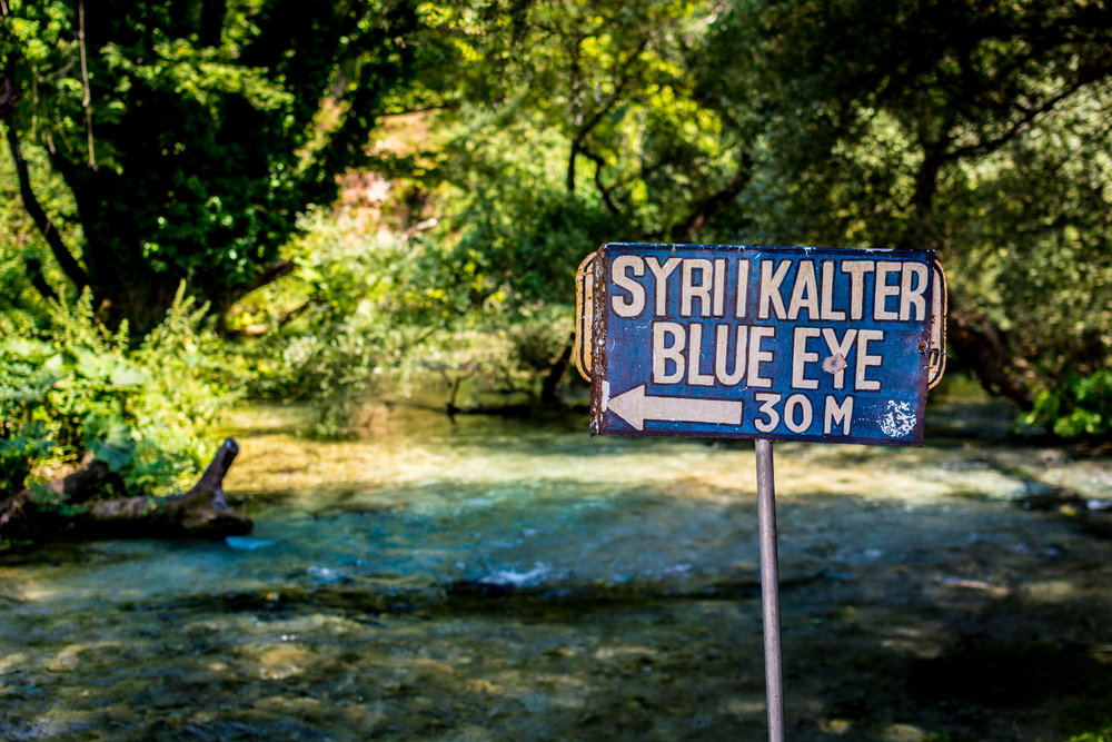Sign to the Blue Eye, with the Bistricë river in the background.