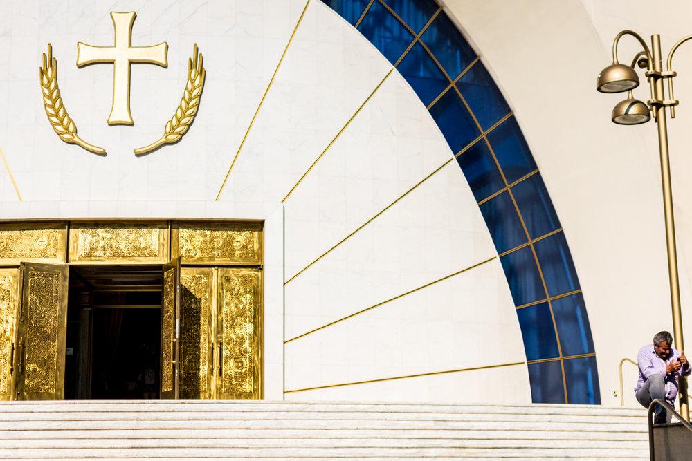 A man checks his phone on the steps of Tirana's massive Orthodox christian church.