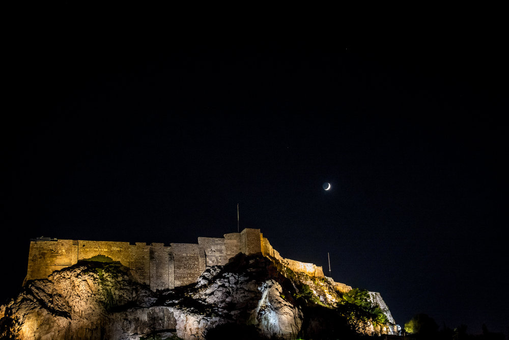 Acropolis lit up at night, under crescent moon.