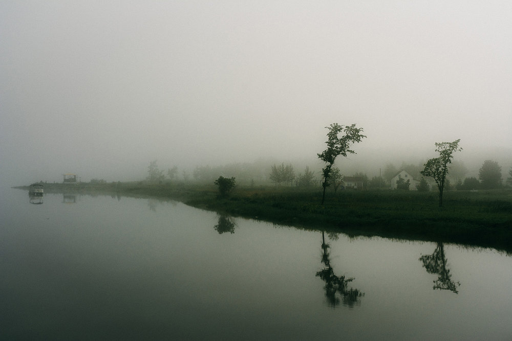 Morning fog shrouds the banks of the Miramichi River.  Buy Print