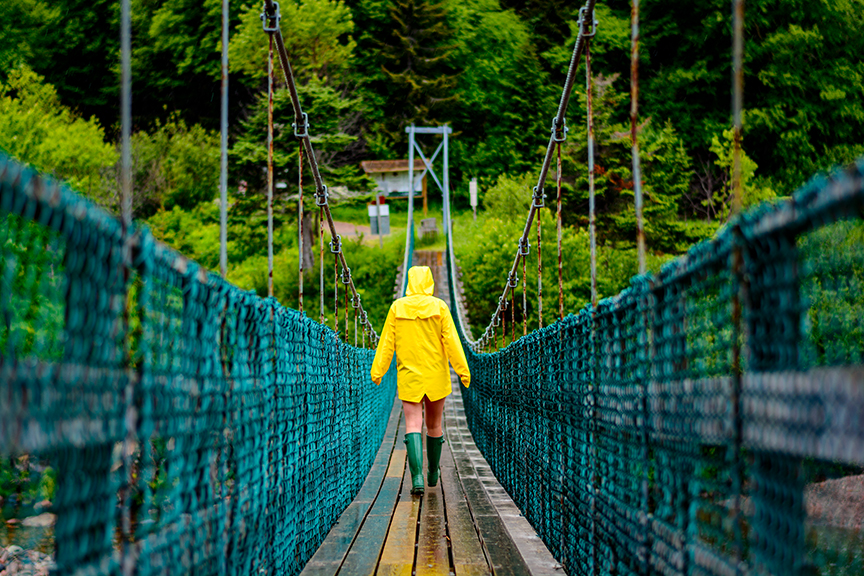 Brianna crosses the Salmon River footbridge outside Saint Martins, New Brunswick.  Buy Print