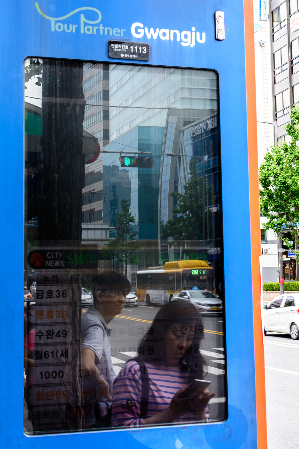 A man and woman wait for a bus in downtown Gwangju.