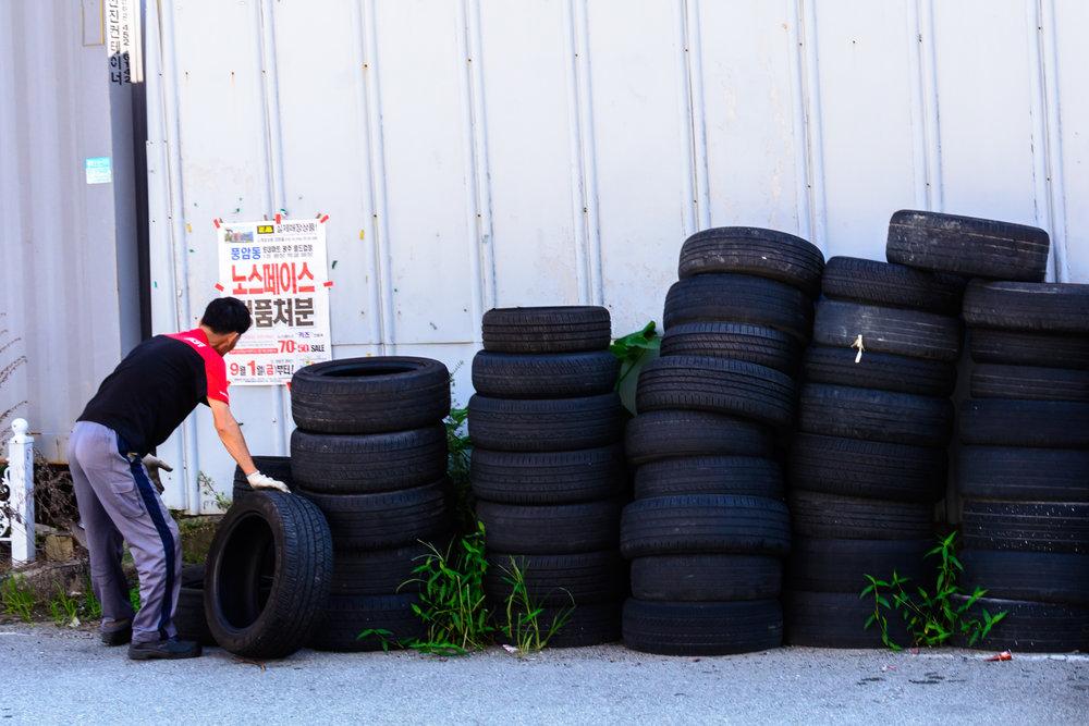 A man stacks tires outside a garage in Geumho 2-dong, Gwangju.
