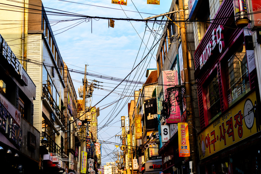 Signs and power lines crisscross above the street near Chonnam University back gate.