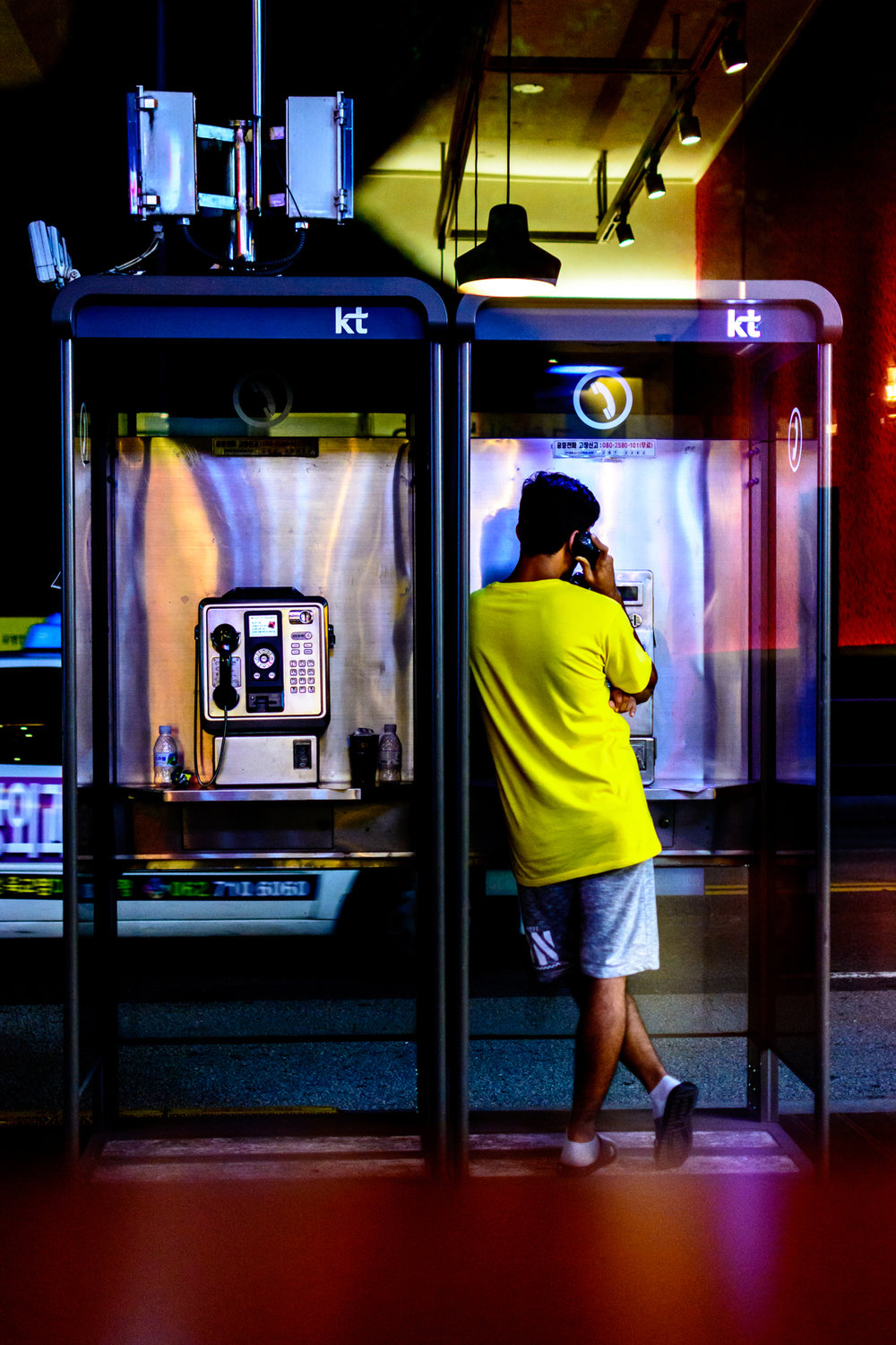 A man makes a call on a payphone near Chonnam University back gate.