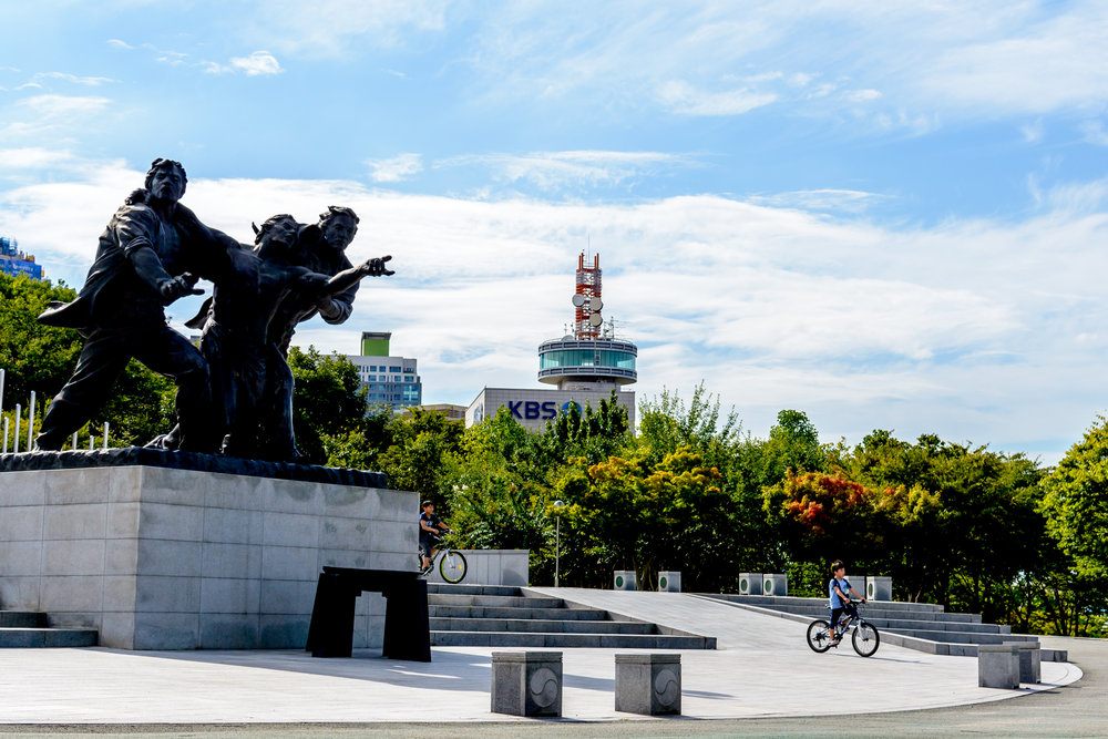 Kids bike through the main plaza of 5.18 Memorial Park in Seo-Gu, Gwangju.