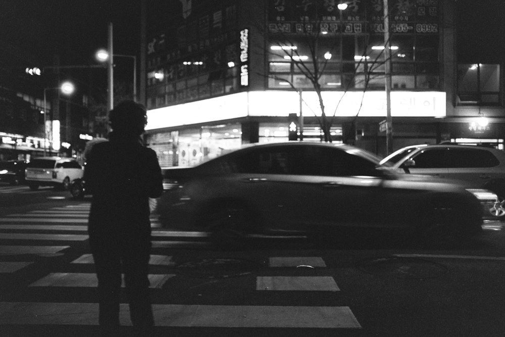 A woman stands silhouetted against traffic.