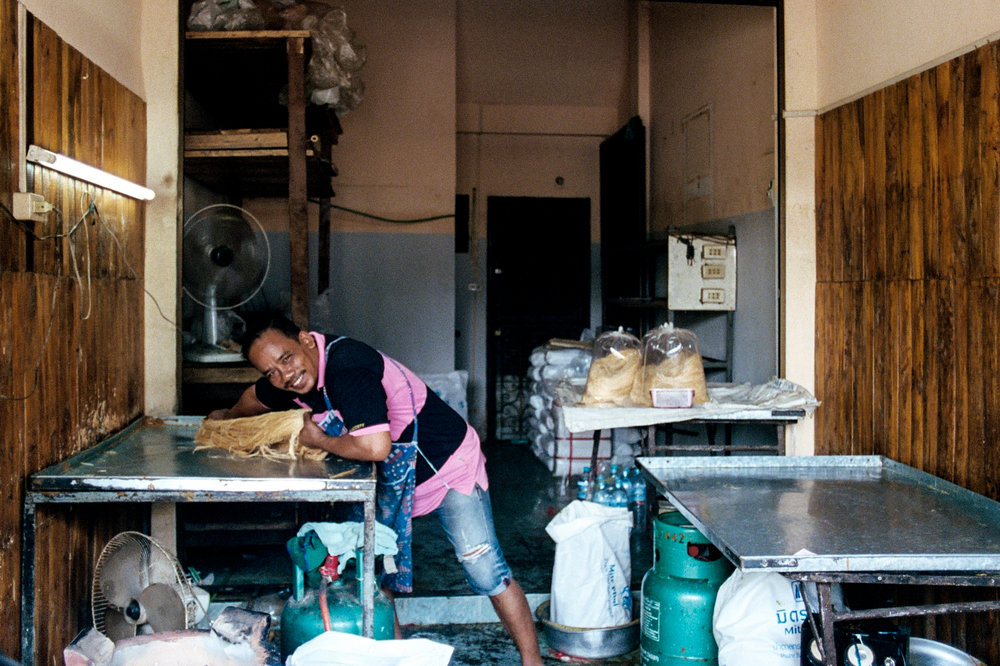 A man makes roti saimai - a Thai sweet similar to cotton candy. Sugar is cooked, then pulled by hand into thin fibers as it cools.