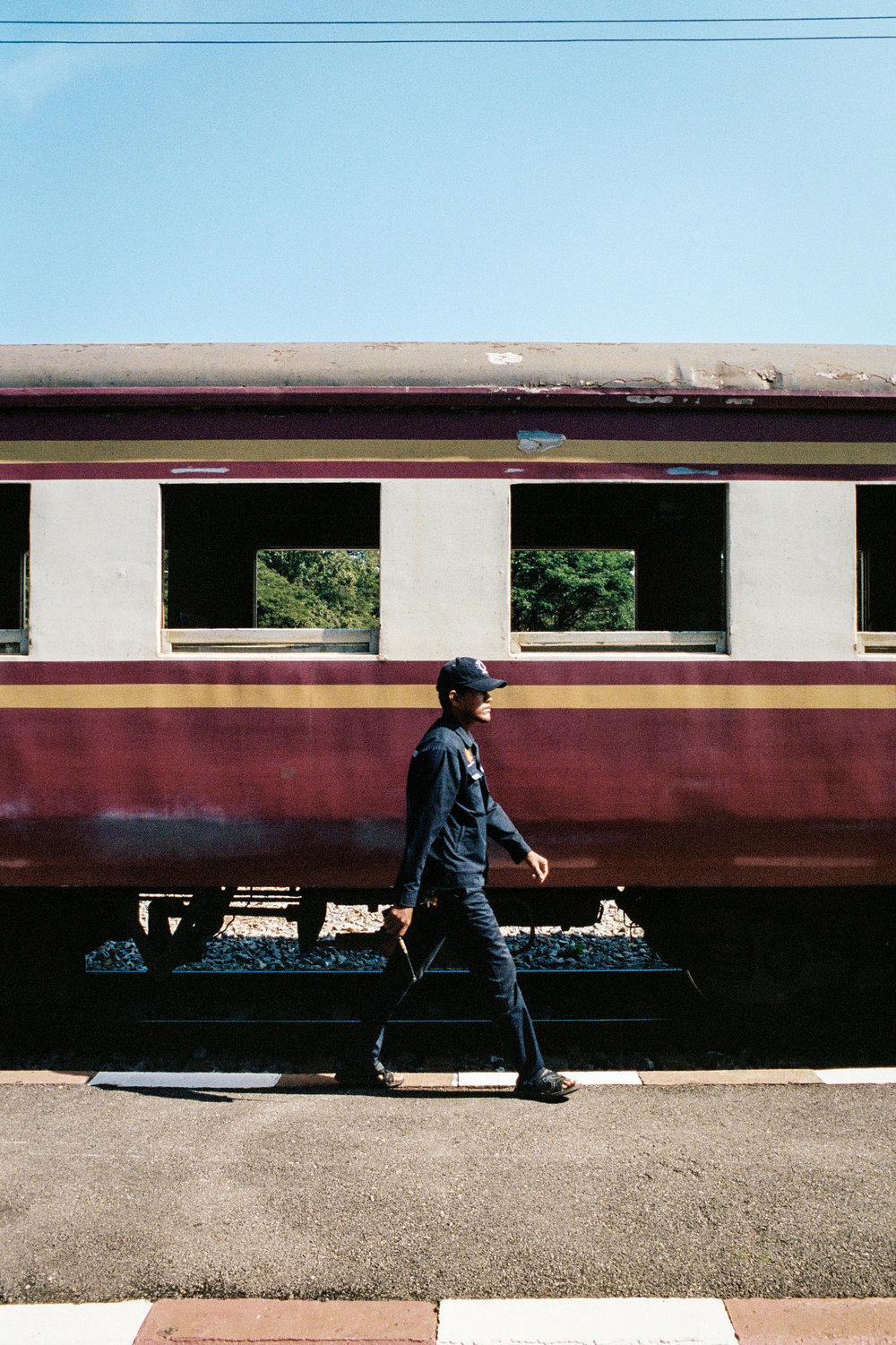A railway official walks along a passenger train in Kanchanaburi. The train runs along a portion of the Burma Railway, built by POWs under Japanese command during WWII. Only a small portion of the railway remains, serving tourists and the local community.