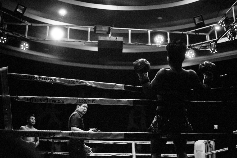 A fighter on the ropes is silhouetted by stadium lights.
