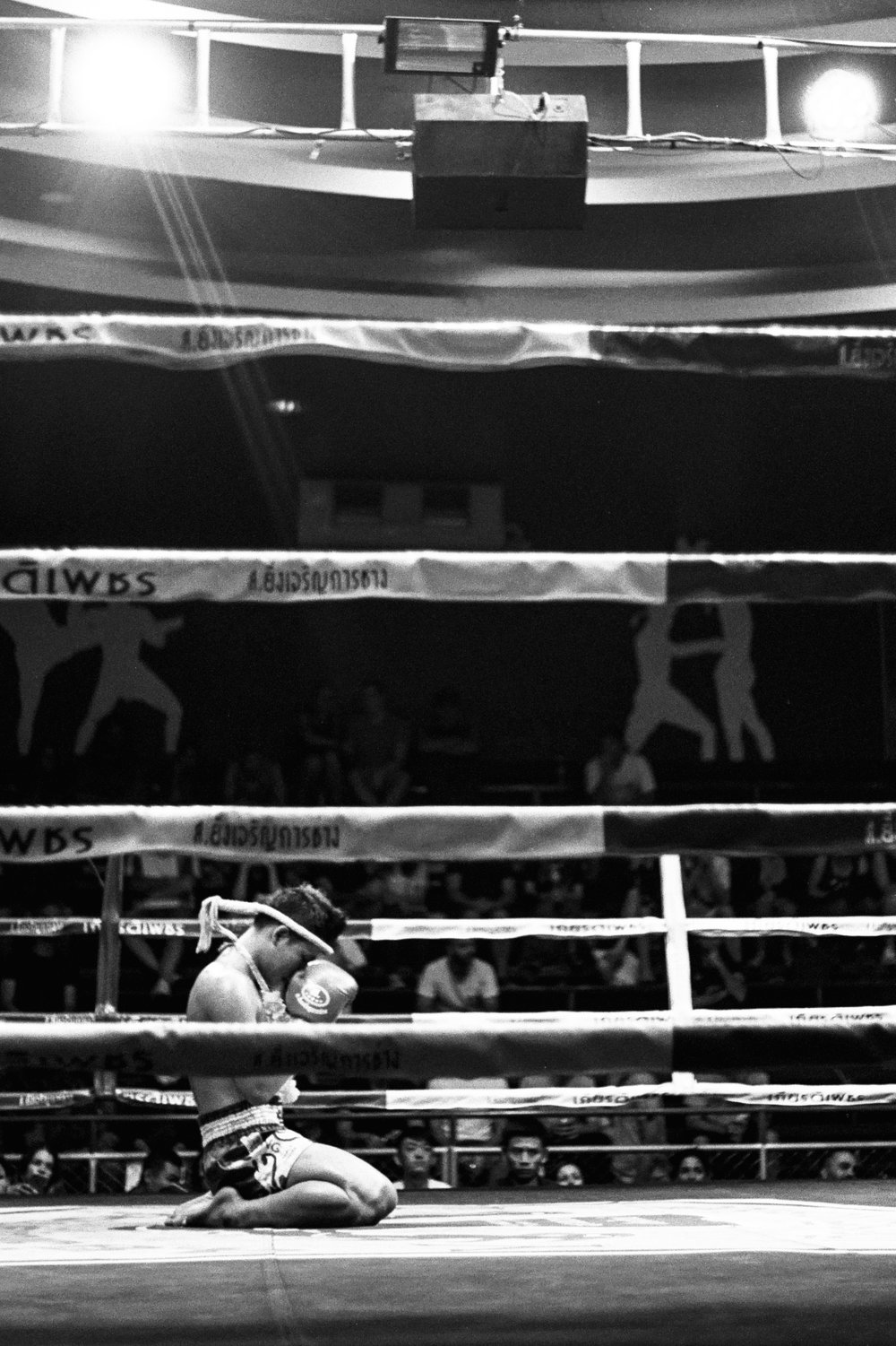 A fighter prays in the ring moments before a Muay Thai fight.
