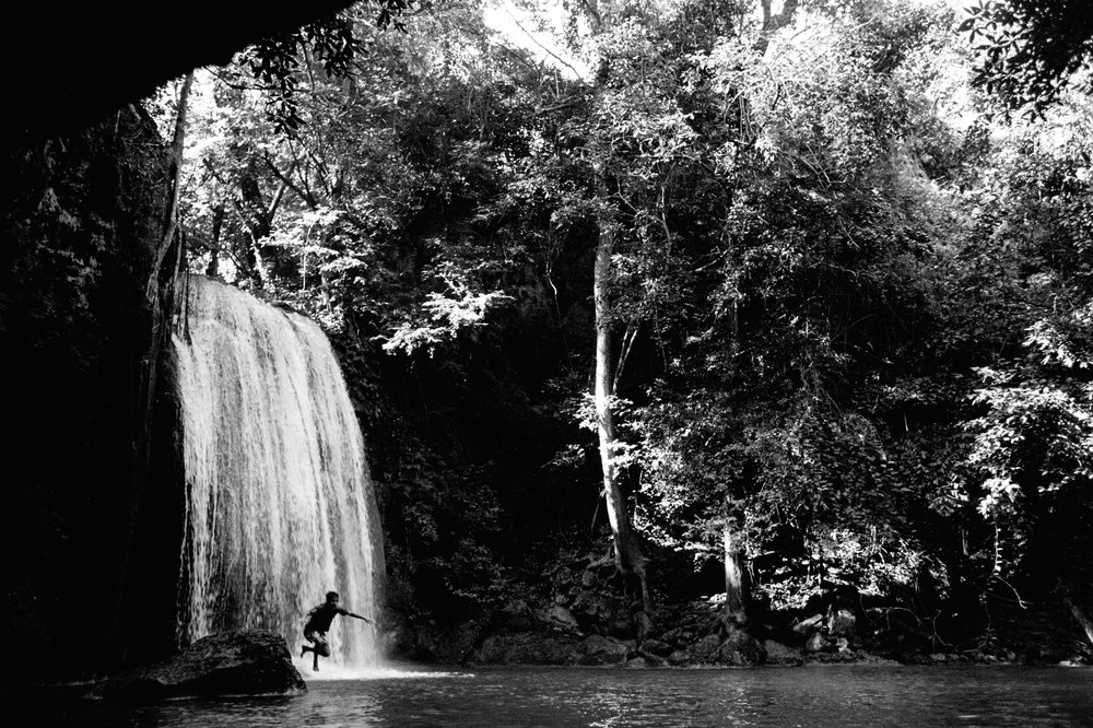 A boy dives into a waterfall pool in Erawan National Park.