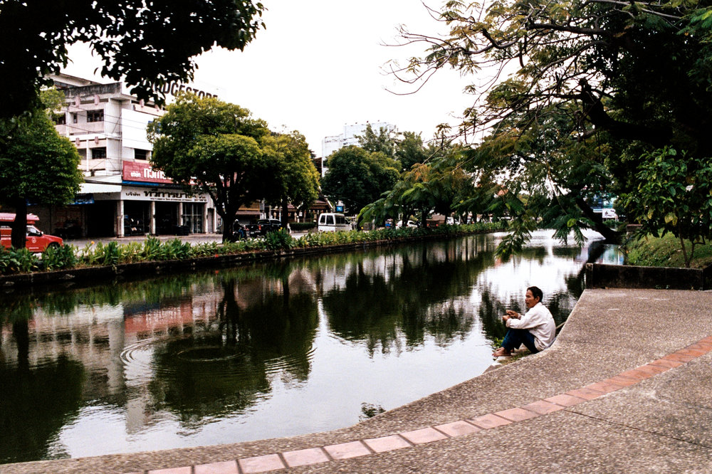 A man relaxes along Chiang Mai's old city canal. Portions of the old city wall still stand along it's route.