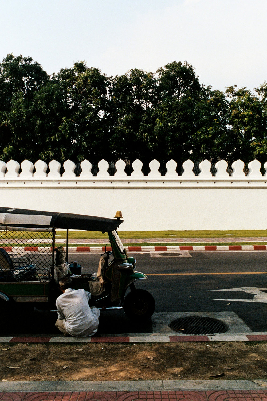 A driver works on his tuk-tuk outside the white walls of Bangkok's Grand Palace.