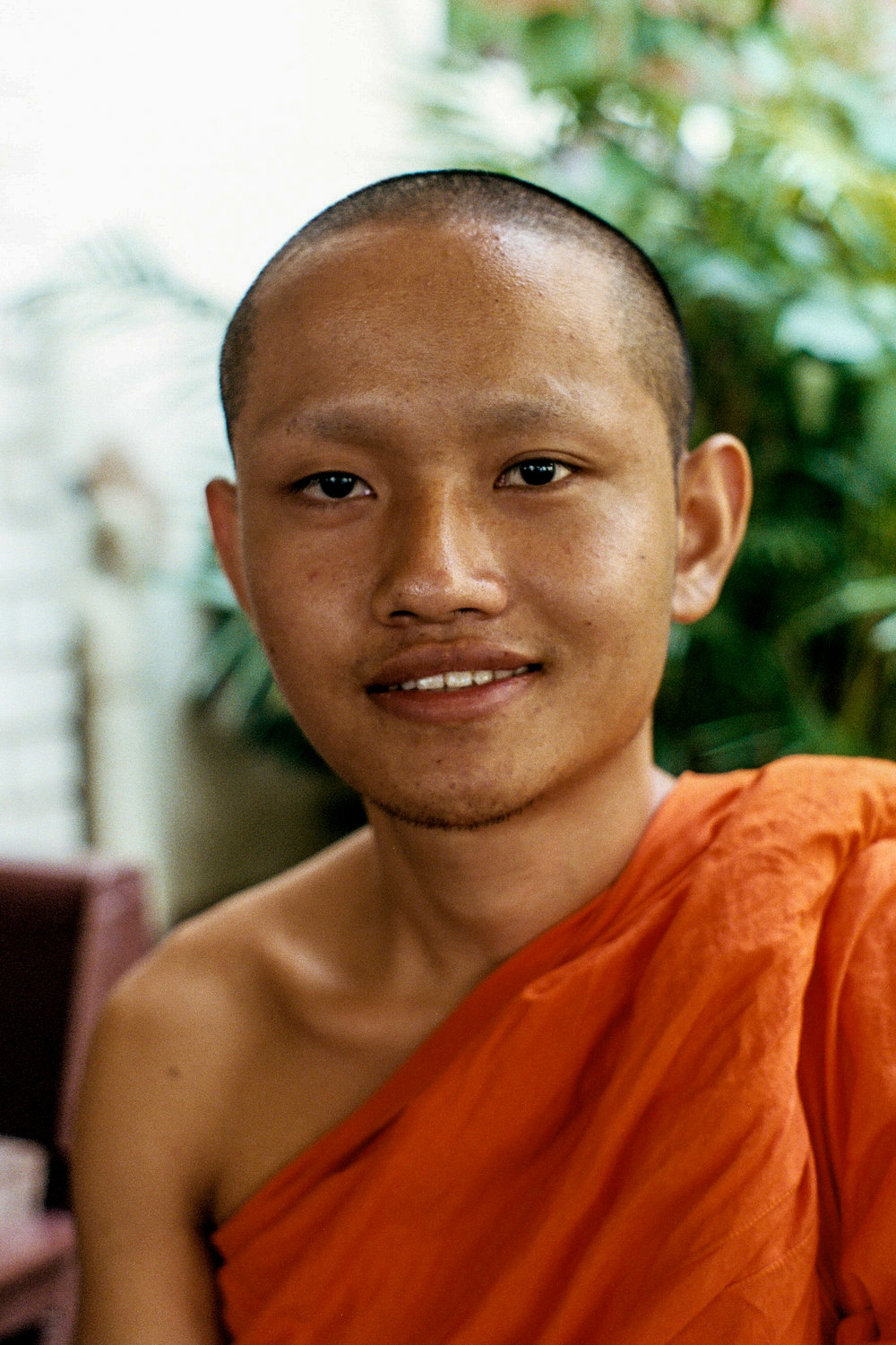 A young monk poses for a portrait. Traditionally, Thai men will serve as a monk for a period in their life. Monks are able to leave at will and may return to being a monk up to three times.